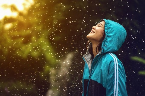 asian-woman-wearing-a-raincoat-outdoors-she-is-happy-picture-id905996586