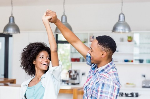 happy-couple-dancing-in-kitchen-picture-id668146926