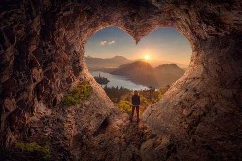 young-woman-in-heart-shape-cave-towards-the-idyllic-sunrise-picture-id873620504