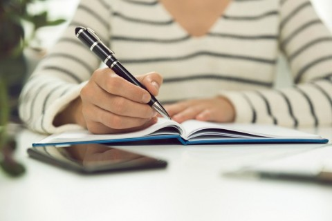 young-business-woman-sitting-at-table-and-writing-in-notebook-on-is-picture-id1001533590