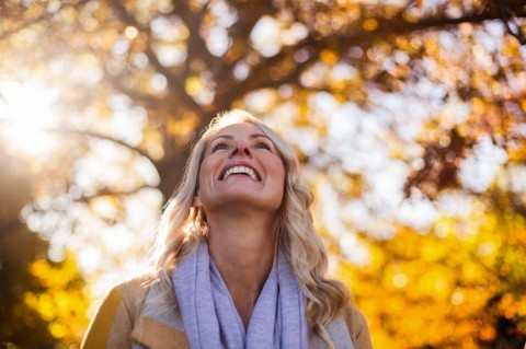 smiling-woman-looking-up-against-trees-picture-id629868062