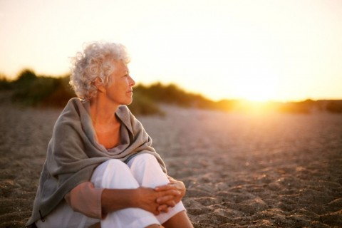 mature-woman-on-beach-looking-into-horizon-picture-id486858785