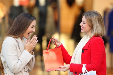 shopper-giving-a-gift-to-a-friend-in-winter-picture-id887389552