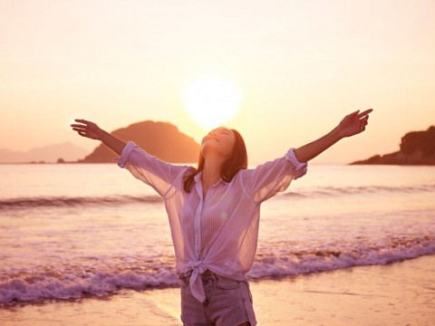 asian-woman-on-beach-enjoying-sunrise-picture-id817359456