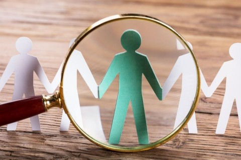 magnifying-glass-on-cutout-figures-picture-id915461616