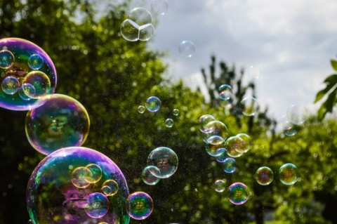 soap-bubbles-floating-on-green-garden-background-picture-id592035670
