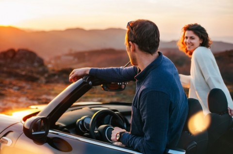 happy-couple-looking-at-sunset-from-convertible-picture-id842605642