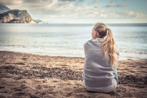 pensive-lonely-young-woman-sitting-on-beach-hugging-her-knees-and-picture-id664047240