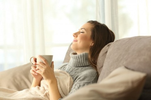 woman-relaxing-at-home-holding-a-coffee-mug-picture-id877068336
