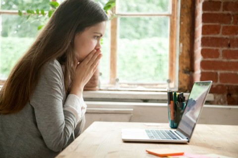 shocked-young-woman-looking-at-laptop-screen-at-work-desk-picture-id870828730