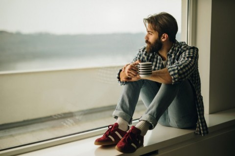 thoughtful-man-drinking-coffee-by-the-window-picture-id856908578