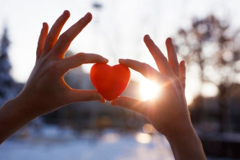 woman-hands-holding-red-heart-at-sunset-picture-id901678548