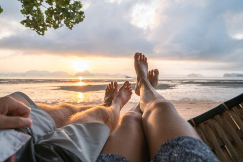 personal-perspective-of-couple-relaxing-on-hammock-feet-view-picture-id910783248