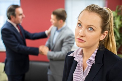 unhappy-businesswoman-with-male-colleague-being-congratulated-picture-id941420838