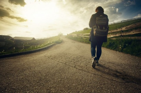 woman-is-walking-on-the-road-at-sunset-picture-id838962412