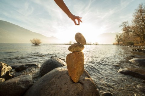 detail-of-person-stacking-rocks-by-the-lake-picture-id501794084