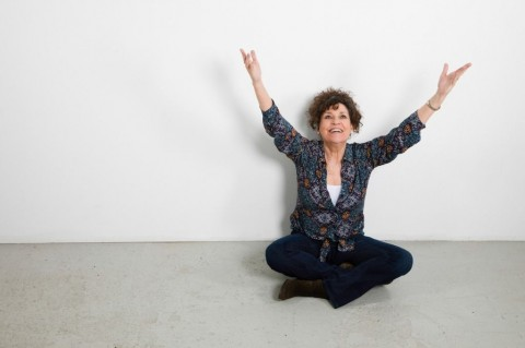 happy-mature-woman-studio-portrait-full-length-sitting-arms-extended-picture-id1128997751