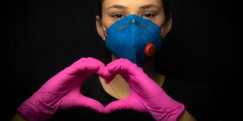 girl-protecting-herself-with-masks-and-gloves-making-a-heart-symbol-picture-id1213944815