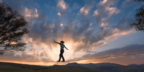 silhouette-of-man-walking-on-slackline-tight-rope-in-the-dusk-picture-id657548446