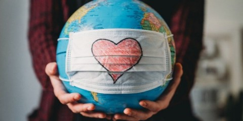 young-woman-holding-a-globe-with-a-face-mask-on-it-heart-shape-is-on-picture-id1216427738