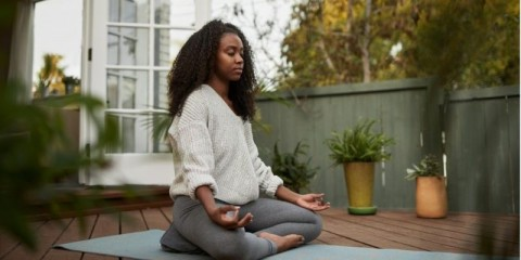 young-woman-sitting-in-the-lotus-pose-outside-on-her-patio-picture-id1202729719