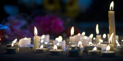 makeshift-memorial-vigil-with-various-size-candles-and-flowers-at-picture-id857856892