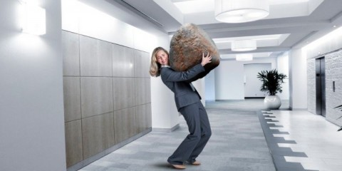 businesswoman-struggles-to-carry-large-stone-in-office-setting-picture-id927530086