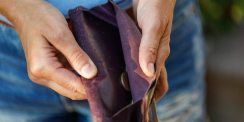 open-purse-with-coins-inside-closeup-as-a-sign-of-lack-of-money-picture-id1031299316