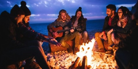 friends-playing-guitar-and-singing-around-bonfire-at-the-beach-picture-id657428556