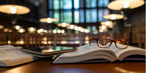 digital-tablet-and-eyeglasses-on-books-in-public-library-picture-id1135144614