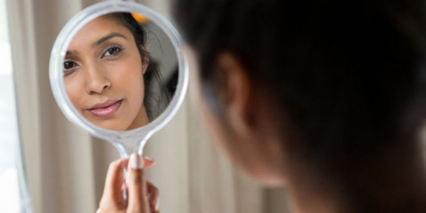 woman-reflecting-on-hand-mirror-picture-id838280698