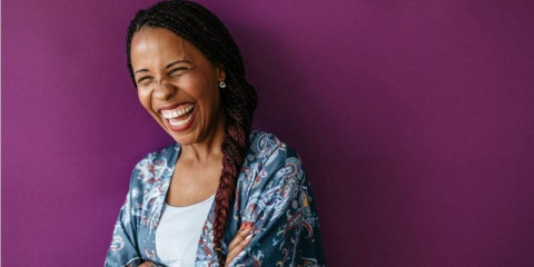 mixed-race-woman-laughing-with-crossed-arms-picture-id1178928986