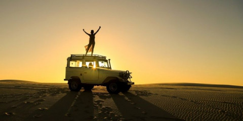 woman-celebrating-on-top-of-offroad-car-picture-id851252520