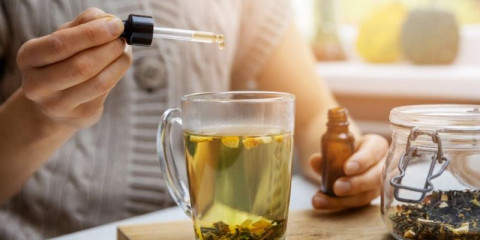 woman-adding-drop-of-cbd-oil-in-cup